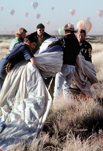 Members of the Navy Hot Air Balloon Team combine their efforts to fold the nylon balloon upon landing during the10th anniversary of the Albuquerque International Balloon Fiesta