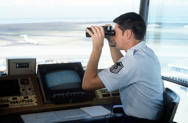 SMSGT Ken Sayler, an air traffic controller, uses binoculars to spot aircraft from his station in the control tower of San Francisco International Airport
