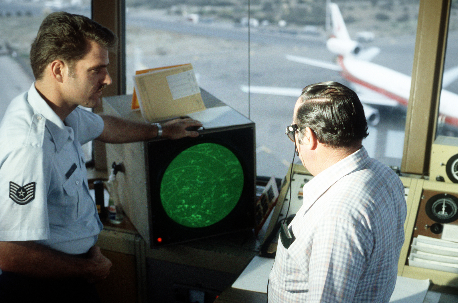 TSGT Fred Crum, an air traffic controller, monitors a radar scope along with his civilian supervisor, at the Oakland Airport Control Tower