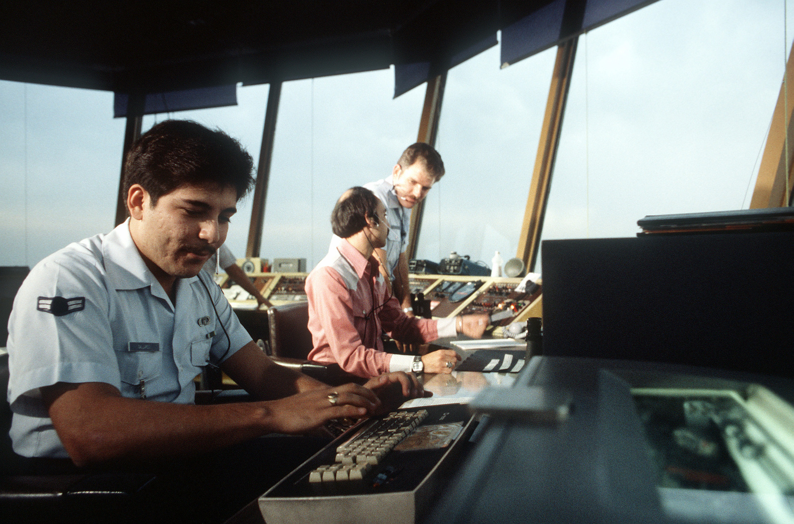 TSGT Fred Crum discusses air traffic control operations with a civilian counterpart, at the Oakland Airport Control Tower
