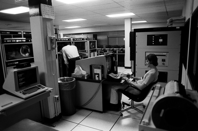 Work in the computer room at the Headquarters, Naval Space Surveillance System goes on around the clock