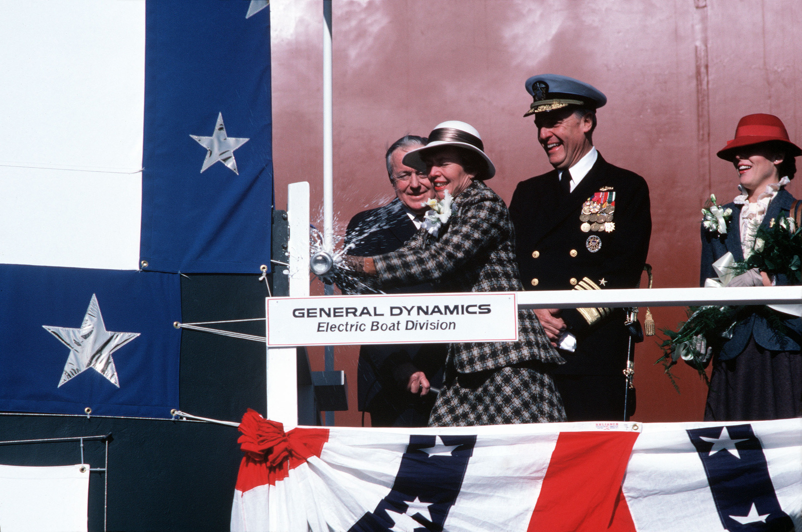 During the launching ceremony Sponsor Sheila McKinney Watkins, Susan Watkin breaks the traditional bottle of champagne over the nuclear-powered strategic missile submarine USS GEORGIA (SSBN 729). Behind her, from left to right, is David S. Lewis, Chairman of the Board at General Dynamics; Admiral James D. Watkins, Chief of Naval Operations, and Maid of Honor Susan Watkins