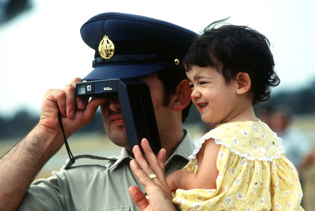 A Royal Australian Air Force member and his child watch an Exercise Sandgroper '82 demonstration during the Open House