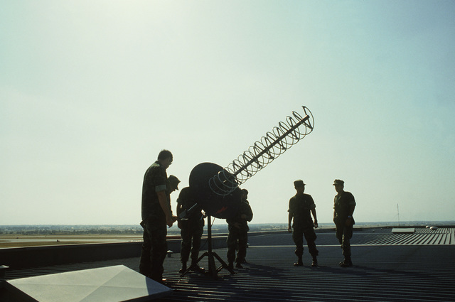 Airmen set up an antenna on the roof of the base operations building for a mobile satellite communications center. The airmen are members of the 1961st Communications Group involved in Exercise Sandgroper '82