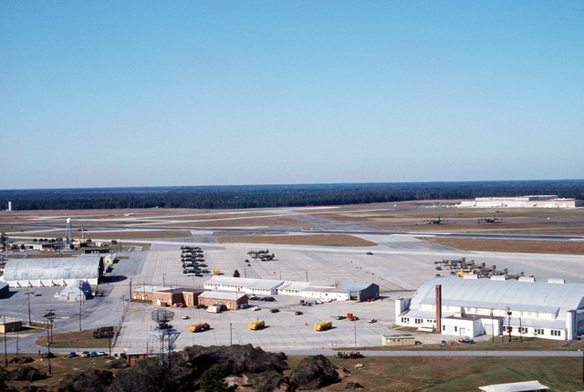 An aerial view of the flight line showing the control and reporting center and aircraft at the Savannah Airport. The aircraft are being prepared for participation in Exercise Quick Thrust '83