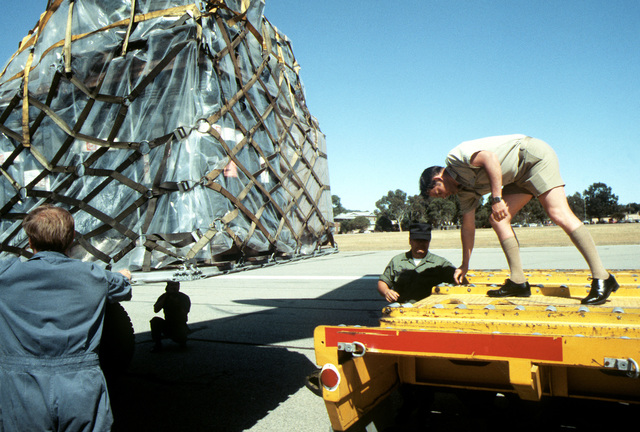 Royal Australian Air Force members help unload a pallet of cargo from a C-141 Starlifter aircraft during Exercise Sandgroper '82