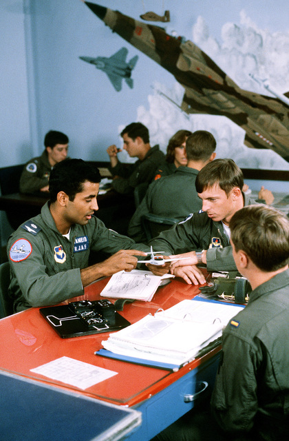 Royal Jordanian Air Force 2LT Mohammed Hameid prepares a flight plan and discusses maneuvers with instructor CPT Bill Silvestri prior to flying a training mission in a T-37 aircraft