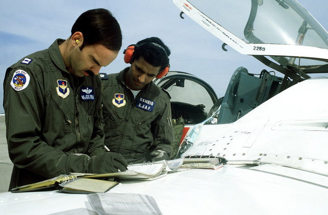 Royal Jordanian Air Force 2LT Mohammed Hameid reviews his flight plan and maneuvers with CPT Tim McGilvra on the wing of a T-37 training aircraft