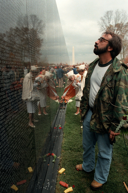 A veteran reads names on the face of the Vietnam Veterans Memorial on the day before its official dedication