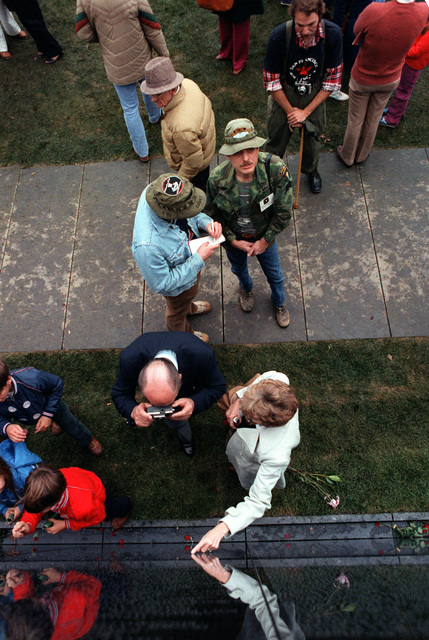 Veterans and visitors search for names on the face of the Vietnam Veterans Memorial on the day before its official dedication ceremony