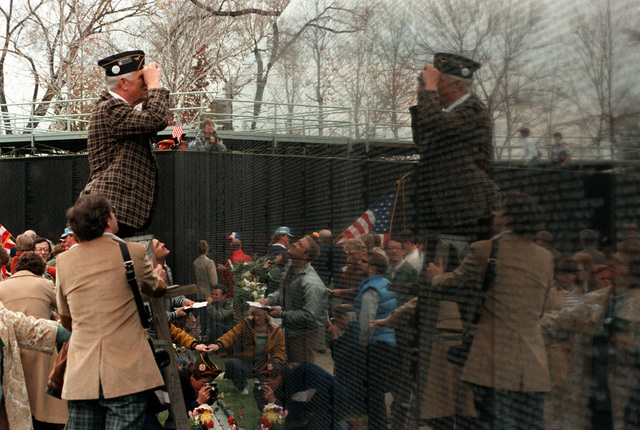 Visitors search for names on the face of the Vietnam Veterans Memorial on the day before its official dedication