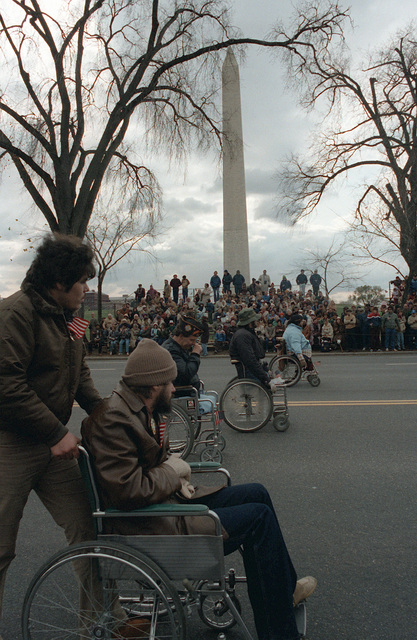 Disabled veterans in wheelchairs pass the Washington Monument during the dedication parade for the Vietnam Veterans Memorial
