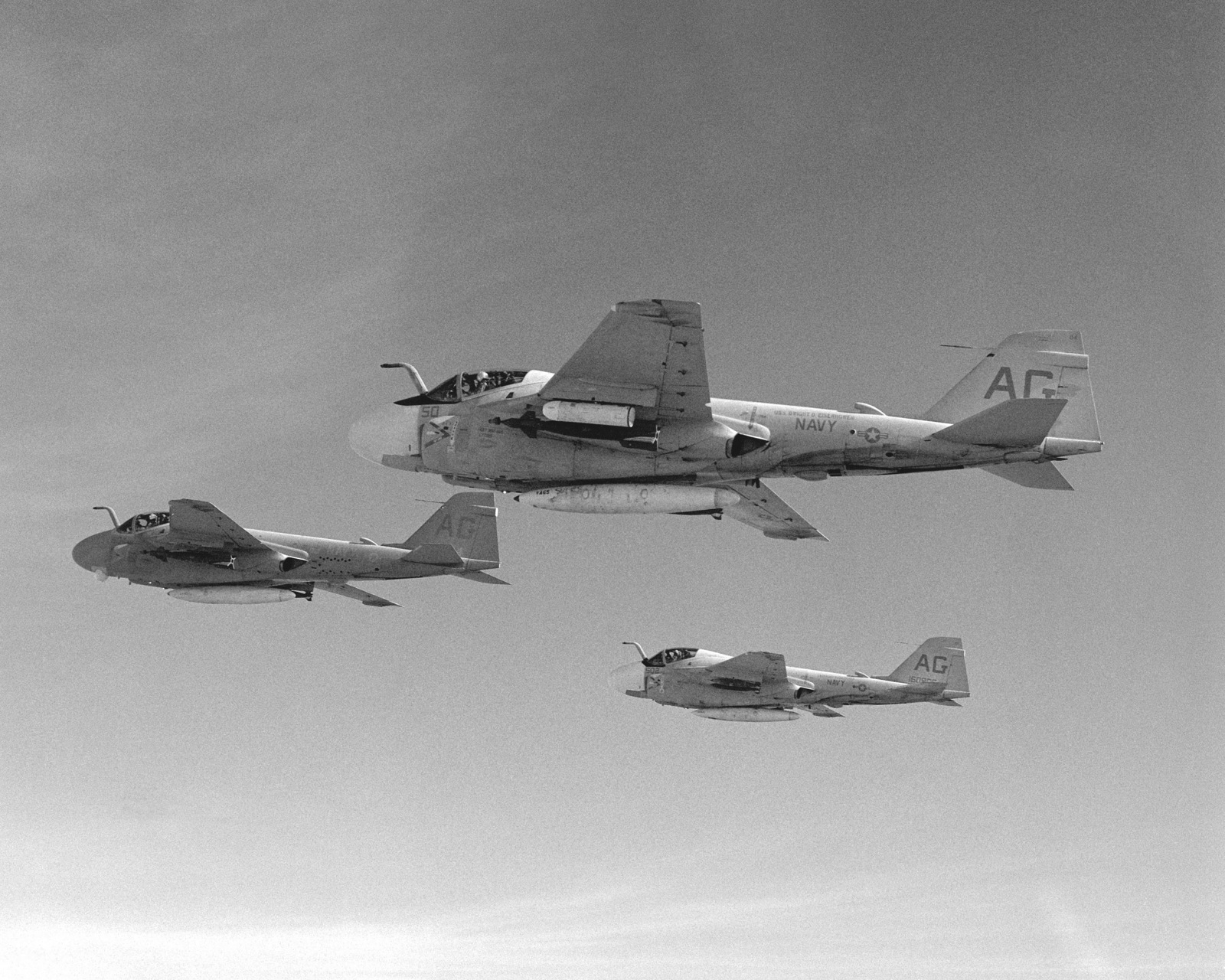 An air-to-air left side view of three A-6E Intruder aircraft with a new tactical paint scheme. They are assigned to Medium Attack Squadron 65 (VA-65)
