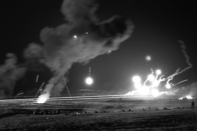 "Aerial flares illuminate the range as Marines fire a volley of tracer rounds during a ""Mad Moment"" at the Basic School"