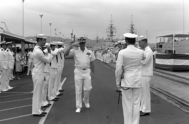 Sideboys exchange salutes with a flag officer as he arrives for the decommissioning of the destroyer USS MORTON (DD-948)