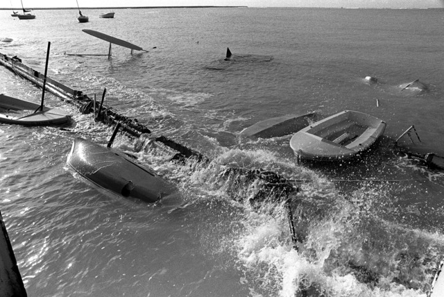 A view of a dock that was destroyed and several small boats that were damaged or capsized in Hickam Harbor during by Hurricane Iwa