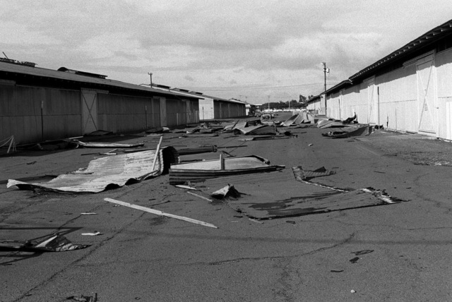 Debris from the roof of Building #1722 blocks a road after Hurricane Iwa passes by