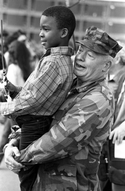Major General Alfred M. Gray Jr., Commanding General, 2nd Marine Division, FMF, helps the son of one of his Marines conduct the Division Band. They were all on hand to welcome home the 32nd Marine Amphibious Unit from Lebanon