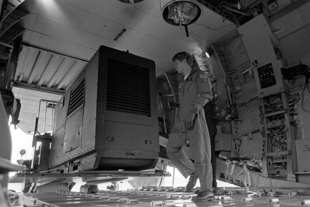The loadmaster of a C-141B Starlifter aircraft guides a portable electric generator into the cargo hold of the aircraft. The generator is being airlifted to Kauai to provide power to areas left without electricity by Hurricane Iwa