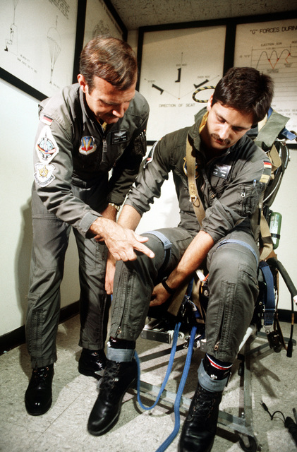 CDR Klaus Pflueger checks LT J.G. Winfried Frank out on the ejection seat of an F-104G Starfighter aircraft during training conducted by the 69th Tactical Fighter Training Squadron. The officers are West German navy pilots