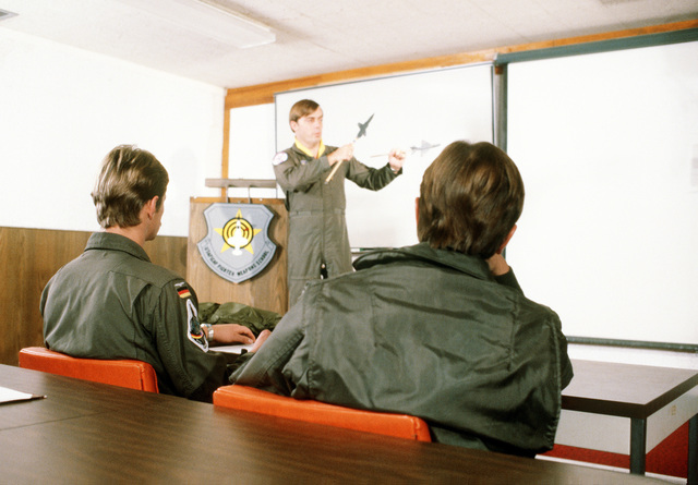 MAJ Dave Bashow of the Royal Canadian Air Force instructs German military pilots on the various flight maneuvers of the F-104G Starfighter aircraft, during training conducted by the 69th Tactical Fighter Training Squadron