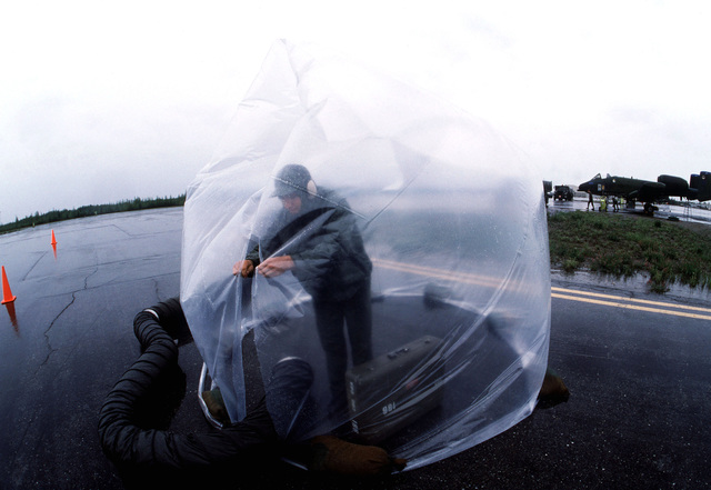 Sergeant Nathan Horne seals the entrance to a plastic dome used by weapons loaders of the 343rd Aircraft Generation Squadron to protect themselves from the extreme cold while they work on the flight line