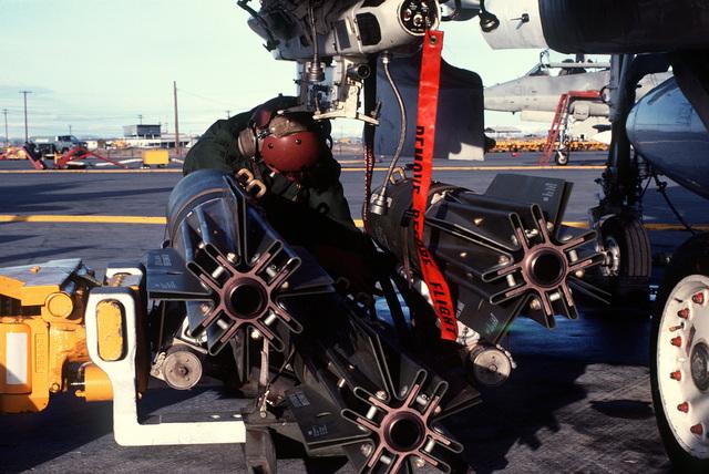 A crewman uploads three Mark 81 general purpose high explosive bombs aboard an A-4F Skyhawk aircraft from Marine Attack Squadron 133 (VMA-133)