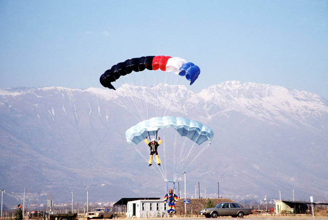 A member of the 1ST Battalion, 509th Airborne Infantry, parachute demonstration team, bottom, and a member of Italy's national parachute demonstration team, Falchi Blu, train together