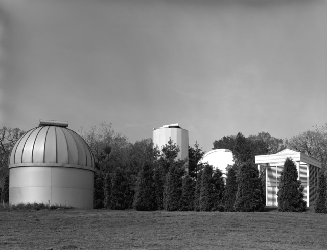 A view from left to right of the double eight-inch Astrograph Dome (B-87), the 26-inch Photographic Zenith Tube (PZT) building (B-90), the 24-inch Telescope Dome and eight-inch PZT building. View is looking west