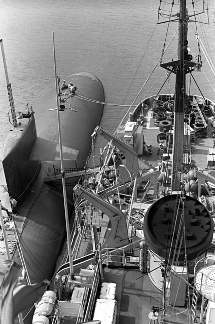 A view of the nuclear-powered attack submarine USS INDIANAPOLIS (SSN-697) and the salvage ship USS CONSERVER (ARS-39) moored abreast, as seen from the crows nest of the CONSERVER. The ships are in port to provide assistance after hurricane Iwa passed through the area