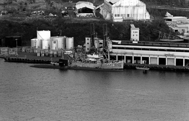 Aerial port view of the nuclear-powered attack submarine USS INDIANAPOLIS (SSN-697) and the salvage ship USS CONSERVER (ARS-39) moored abreast. The ships are in port to provide assistance after hurricane Iwa passed through the area