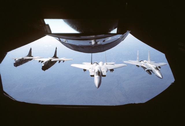 An air-to-air view, as seen from the boom section of a KC-135A Stratotanker aircraft, of two A-7D Corsair II aircraft (left) and two F-15 Eagle aircraft as they approach for refueling