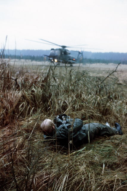"""CAPT. Frank Gray, a """"survivor"""" of a downed aircraft watches as two HH-53 Super Jolly helicopters from the 67th Aerospace Rescue and Recovery Squadron arrive to rescue him during pararescue training"""