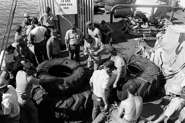 Crewmen aboard the salvage ship USS CONSERVER (ARS-39) attach lines to tires as they prepare to lower them over the side. The CONSERVER is in port to salvage a Coast Guard boat that sank when hurricane Iwa passed through the area