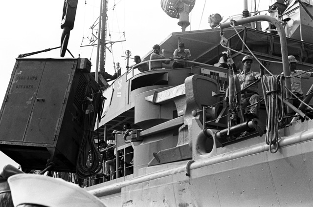 Crewmen aboard the salvage ship USS CONSERVER (ARS-39) prepare to lower a portable generator over the side. The CONSERVER is in port to assist after hurricane Iwa passed through the area