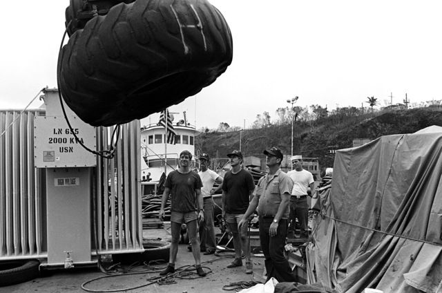 Crewmen aboard the salvage ship USS CONSERVER (ARS-39) prepare to lower tires over the side. The CONSERVER is in port to salvage a Coast Guard boat that sank when hurricane Iwa passed through the area