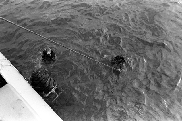 Crewmen from the salvage ship USS CONSERVER (ARS-39) position a tire in the water, as they prepare to begin salvage operations on a Coast Guard boat that sank when hurricane Iwa passed through the area