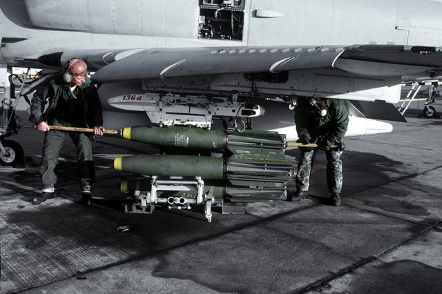 Crewmen upload three Mark 81 general purpose high explosive bombs aboard an A-4F Skyhawk aircraft from Marine Attack Squadron 133 (VMA-133)