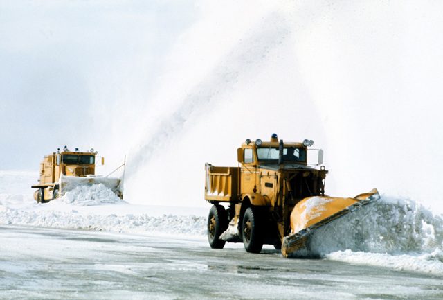 Snow removal vehicles clear a runway on the NATO base