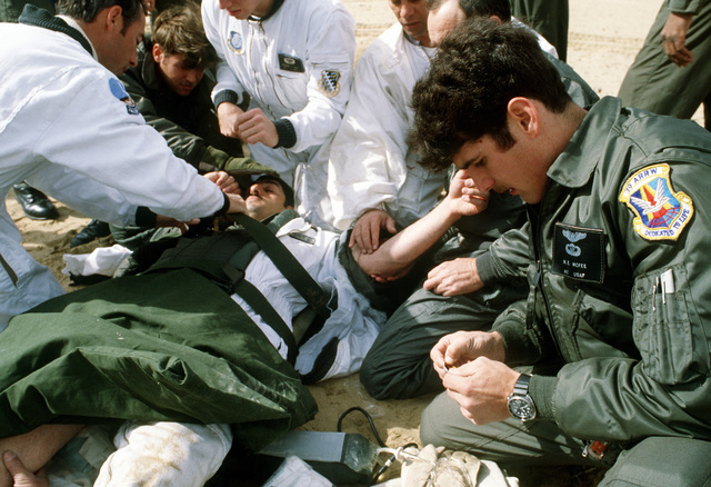 TSGT Tony Biondo is treated for a broken thigh bone after his main parachute malfunctioned, during a jump at the Flight Test Center
