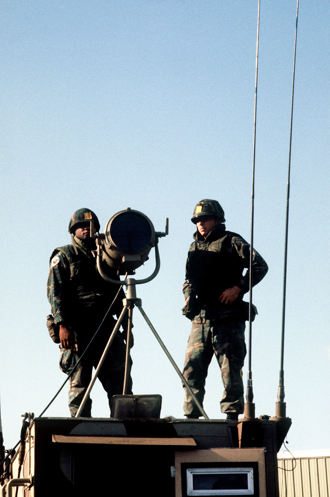 Two Marines from the 32nd Marine Amphibious Unit (32nd MAU) stand watch on the roof of a mobile communications station, during a multinational peacekeeping operation. The unit was sent here after a confrontation took place between Israeli forces and the Palestine Liberation Organization