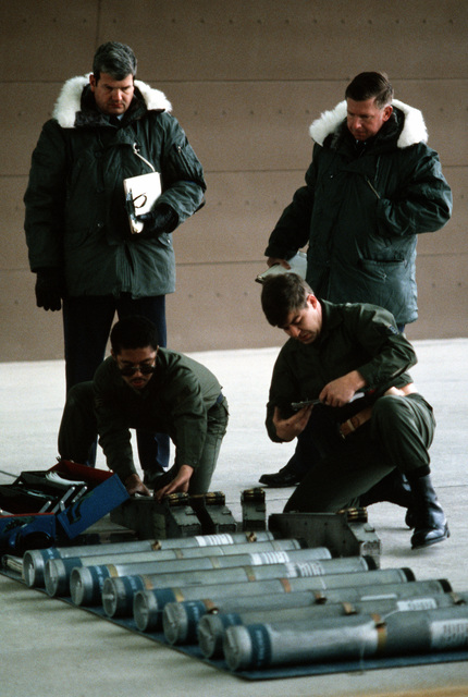 MAJ Applewhite and SMSGT Driscoll, competition judges, observe as A1C Franklin and SSGT Klobetanz check over 7.62mm shells and white phosphorus rocket canisters prior to loading them into their OV-10A Bronco aircraft during munitions loading competition Sabre Spirit I