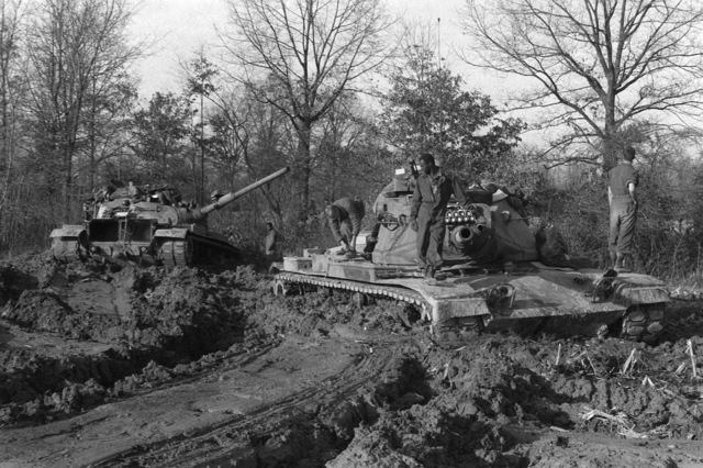 Two M-60A1 tanks from Company B, 4th Battalion, 37th Armor, Fort Knox, Kentucky, are stuck in a muddy cornfield near Normandy Loop during Exercise EAGLE STRIKE III