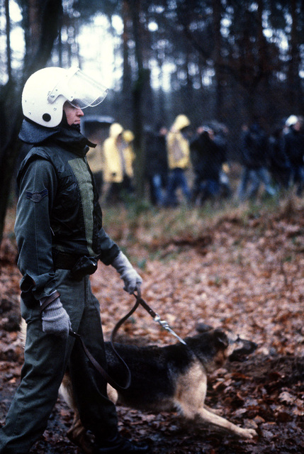 AIRMAN 1ST Class Kenneth Liddle and his canine partner move along parallel to protesters marching outside the perimeter fence. The protesters are demonstrating peacefully against NATO's decision to deploy Pershing II and cruise missiles in Western Europe