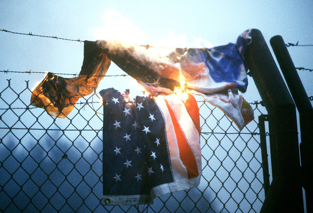 An American flag is burned on the perimeter fence by protesters demonstrating against NATO's decision to deploy Pershing II and cruise missiles in Western Europe