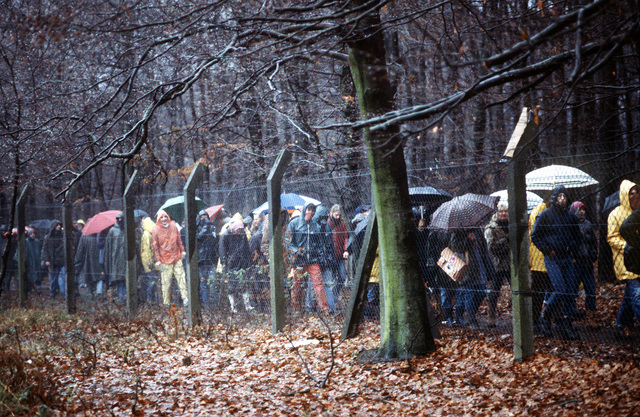 Protesters march in the rain outside the perimeter fence. The protesters were part of a group of approximately 300 who were demonstrating peacefully against NATO's decision to deploy Pershing II and cruise missiles in Western Europe
