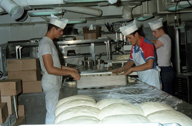Mess management specialists prepare food in the bakery aboard the nuclear-powered aircraft carrier USS ENTERPRISE (CVN 65)