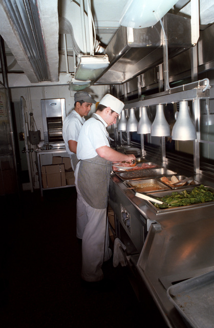 Mess management specialists prepare food in the enlisted dining facility aboard the nuclear-powered aircraft carrier USS ENTERPRISE (CVN 65)