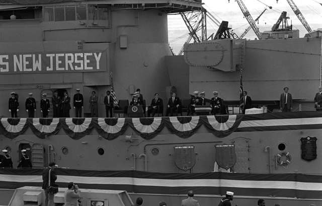 A view of the speakers platform mounted aboard the deck of the battleship USS NEW JERSEY (BB-62) during the recommissioning ceremony for the battleship. Seated behind the speakers platform, to the right, is Secretary of the Navy John F. Lehman Jr. and President Ronald Reagan