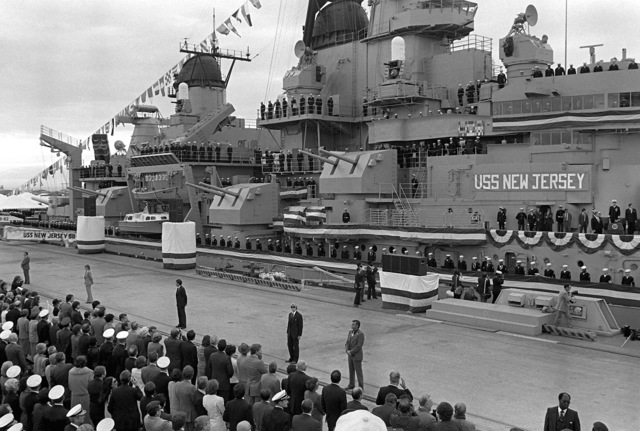 An overall view of the commissioning ceremony for the battleship USS NEW JERSEY (BB-62) as crewmen man the rail